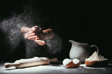 cropped shot of chef clapping ahnds with flour before making dough on black