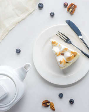 top view of appetizing piece of cake with meringue and teapot on white table