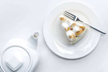 top view of teapot and delicious piece of cake with meringue on white table