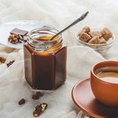 Photo appetizing jar of caramel jam and cup of coffee on tablecloth