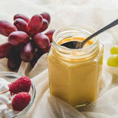 Photo appetizing jar of honey with grapes on tablecloth