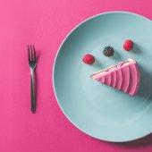 pohled shora kusu růžový dort s ovocem na štítku na růžové povrchu