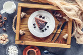 top view of appetizing piece of chocolate cake on plate on wooden tray