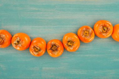 top view of row of persimmons on turquoise wooden table