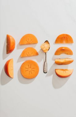 top view of persimmons pieces and spoon on white