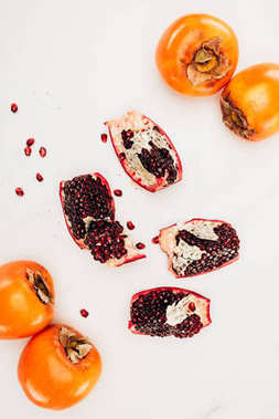 top view of persimmons and pomegranates isolated on white
