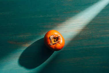 top view of persimmon on table with light and shadow