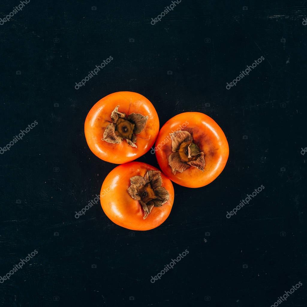 top view of three persimmons isolated on black
