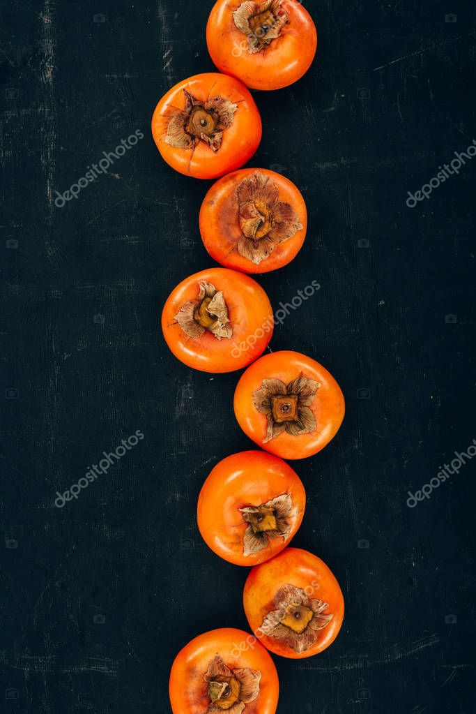 top view of row of persimmons on black
