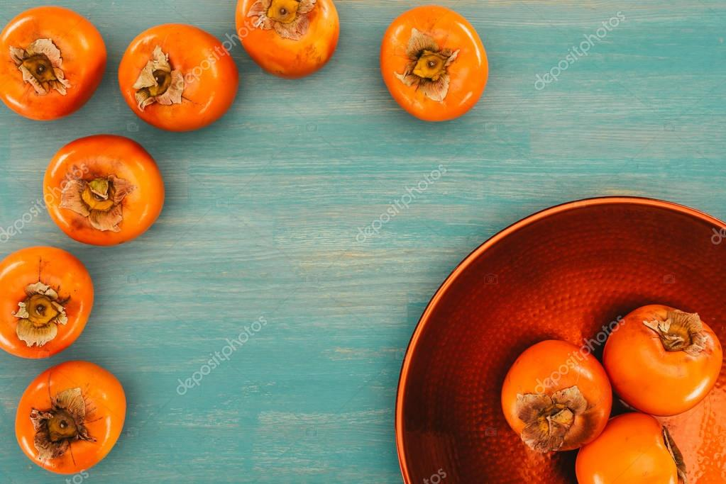 top view of persimmons on red plate and turquoise table