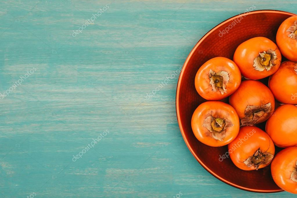 top view of persimmons on red plate on turquoise table