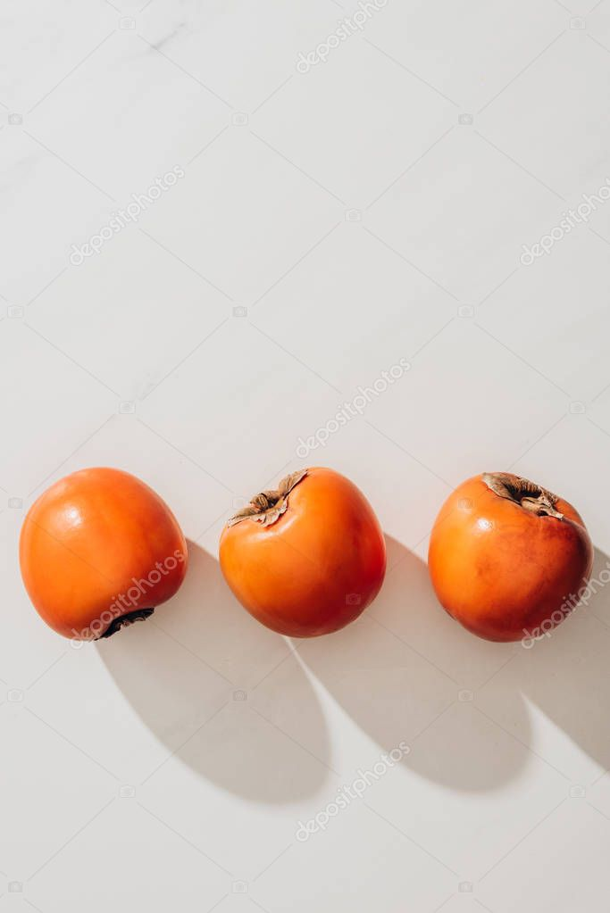 top view of three ripe persimmons on white