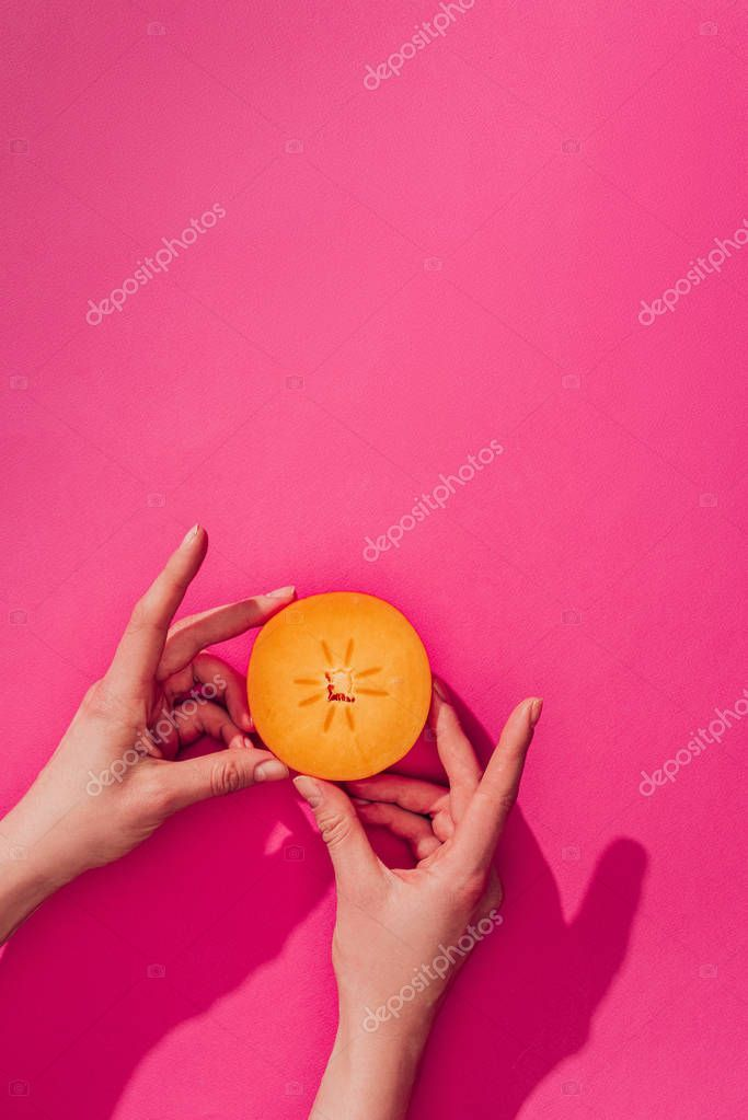 cropped image of woman holding persimmon piece on pink