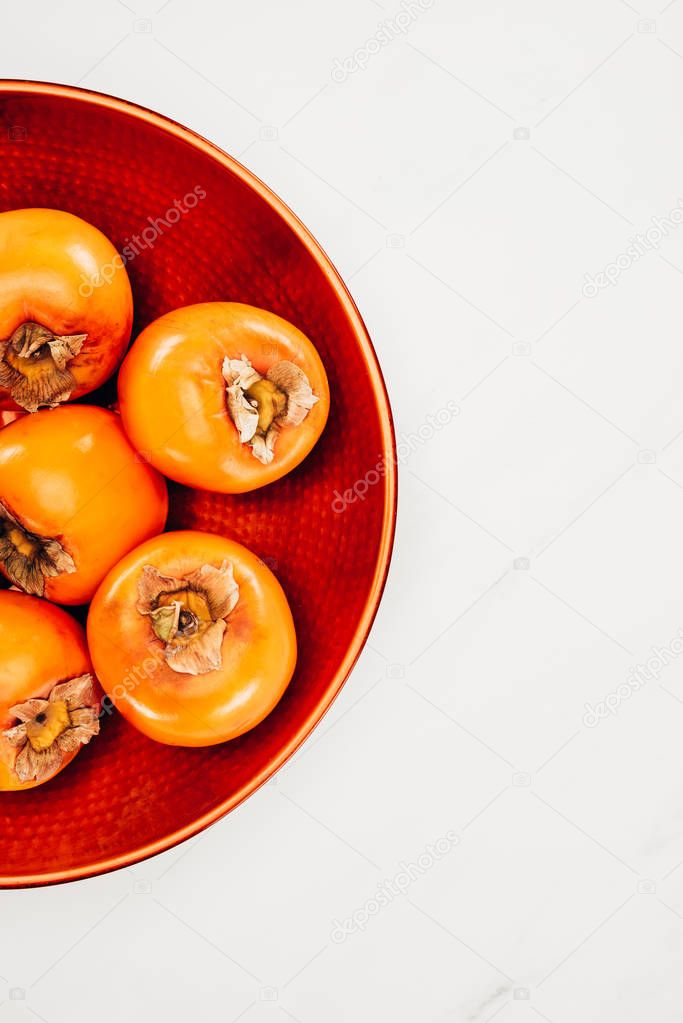 top view of persimmons on red plate isolated on white