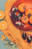 Fotografie top view of yummy fruits on plate on orange tablecloth
