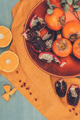 Fotografie top view of ripe fruits on plate on orange tablecloth