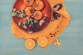 Fotografie top view of persimmons with cut oranges and pomegranates on plate on orange tablecloth