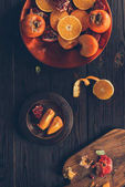 Photo top view of cut persimmons with oranges and pomegranates on plates