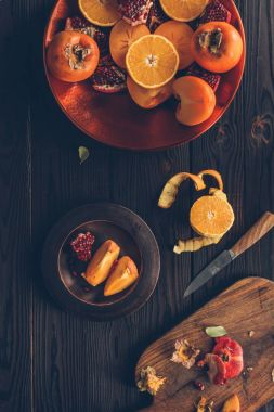 top view of fruits and cutting board with knife on table
