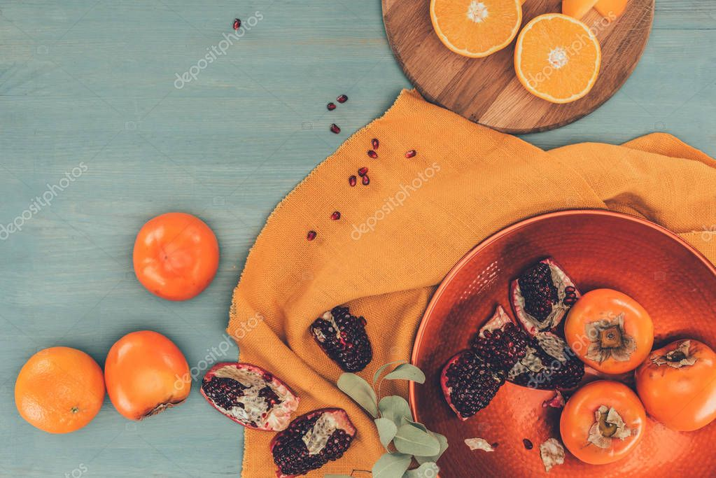 top view of persimmons with oranges and pomegranates on turquoise table