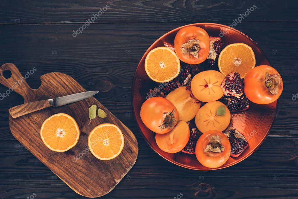 top view of fruits on plate and wooden board