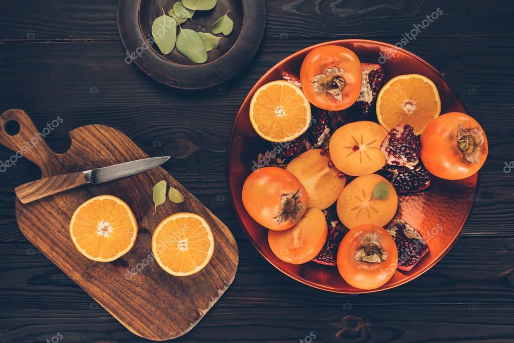 top view of persimmons with cut oranges and pomegranates on plates and wooden board