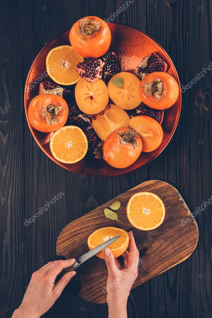 cropped image of woman cutting orange on wooden board