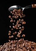 Kaffeebohnen fallen von einem Löffel auf einen Haufen, isoliert auf schwarz