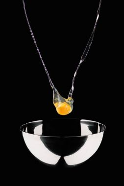 chicken egg falling into bowl isolated on black