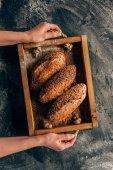 oříznuté záběr ženy držící dřevěný box s šišky chleba v rukou