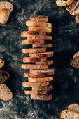 Fotografie top view of arranged pieces of bread on dark tabletop with flour