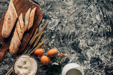 top view of arranged pieces of french baguette, raw eggs, wheat and flour in bowl on dark surface