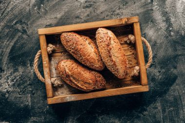 top view of arranged loafs of bread in wooden box on dark tabletop with flour