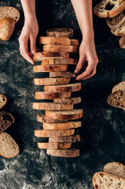 cropped shot of female hands and arranged pieces of bread on dark surface with flour