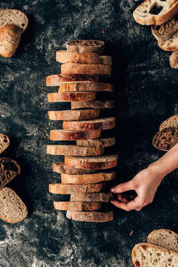 cropped shot of female hand and arranged pieces of bread on dark surface with flour