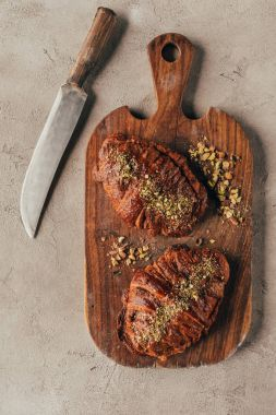 Top view of freshly baked croissants with pistachio nuts on wooden cutting board and knife on light surface