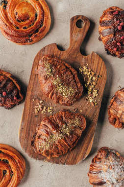 Flat lay with freshly baked sweet croissants with pistachio nuts on wooden cutting board on light surface