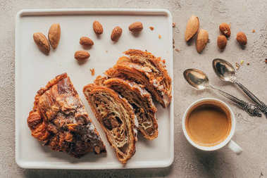 top view of cup of coffee and sweet pastry with almonds on plate on light tabletop