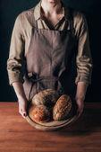Fényképek részleges kilátás nyílik tartó női loafs kenyér elszigetelt fekete fa vágódeszka