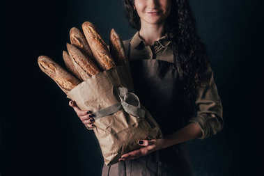 cropped shot of woman in apron holding french baguettes in paper bag in hands isolated on black