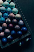 Fotografie top view of colored painted easter eggs in wooden box on dark table