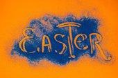 Fotografie pohled shora velikonoční znamení z modré písku na oranžového povrchu