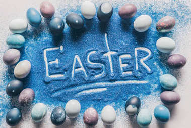 top view of easter sign made of blue sand with painted eggs on white