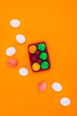 top view of colored easter eggs in red egg tray isolated on orange