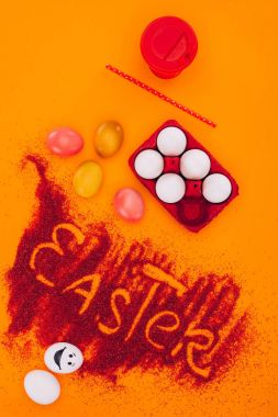 top view of easter sign made of red sand with chicken eggs and coffee on orange
