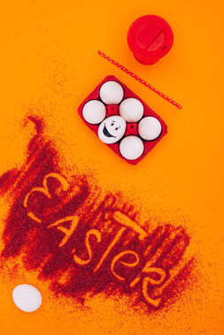top view of easter sign made of red sand with chicken eggs with smiley on orange