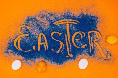 top view of easter sign made of blue sand with chicken eggs on orange