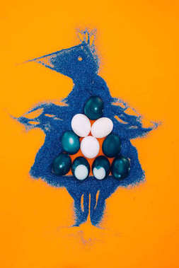top view of blue easter chicken made of sand with painted eggs isolated on orange