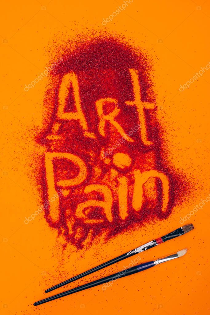 top view of art pain sign made of red sand and brushes isolated on orange