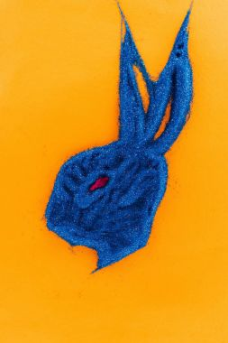 top view of easter bunny made of blue sand isolated on orange